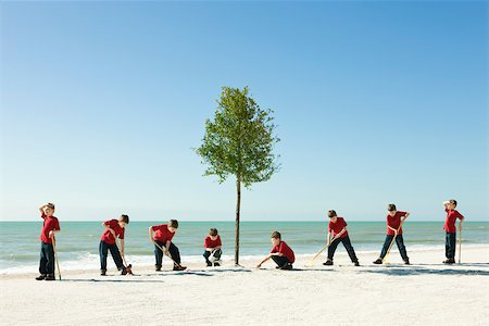 Boy caring for tree planted on sandy beach Stock Photo - Premium Royalty-Free, Code: 632-03500774