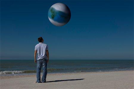 Man on beach looking up at alien world orbiting overhead Stock Photo - Premium Royalty-Free, Code: 632-03500785