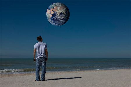 Man on beach looking up at planet earth orbiting overhead Stock Photo - Premium Royalty-Free, Code: 632-03500787