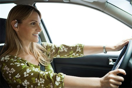 Driving while using hands free bluetooth earpiece Stock Photo - Premium Royalty-Free, Code: 632-03500895