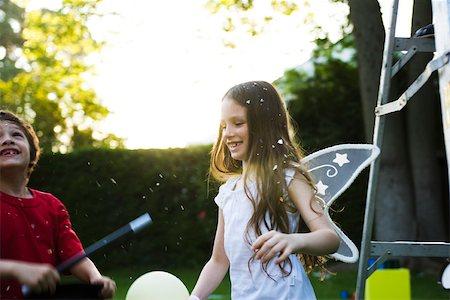 Children having fun under falling confetti Stock Photo - Premium Royalty-Free, Code: 632-03501020