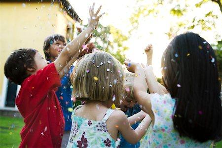Children showered in falling confetti Stock Photo - Premium Royalty-Free, Code: 632-03501022