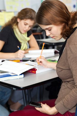 Young woman text messaging while in class Stock Photo - Premium Royalty-Free, Code: 632-03516554
