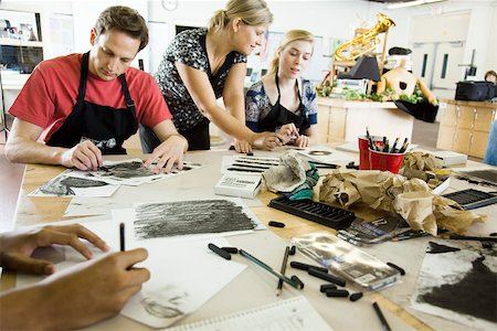 Art teacher assisting students with charcoal drawings Stock Photo - Premium Royalty-Free, Code: 632-03516633