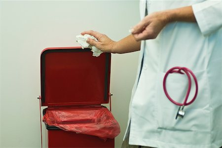 Discarding waste in medical waste bin Stock Photo - Premium Royalty-Free, Code: 632-03516751