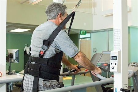 rehabilitation - Man exercising on treadmill with assistance of rehabilitation harness supporting body weight Stock Photo - Premium Royalty-Free, Code: 632-03516778