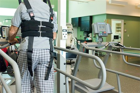 rehabilitation - Man exercising on treadmill with assistance of rehabilitation harness supporting body weight Stock Photo - Premium Royalty-Free, Code: 632-03516786