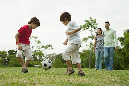 Boys playing soccer, parents watching in background Stock Photo - Premium Royalty-Free, Code: 632-03516975