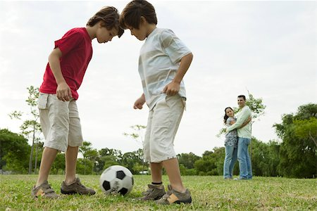 Boys playing soccer, parents embracing in background Stock Photo - Premium Royalty-Free, Code: 632-03516993