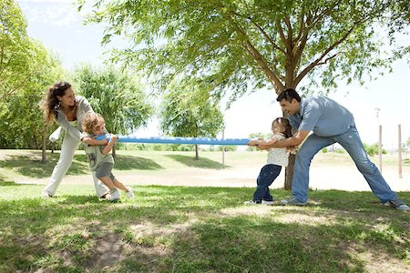 Family playing tug-of-war in park Stock Photo - Premium Royalty-Free, Code: 632-03517003