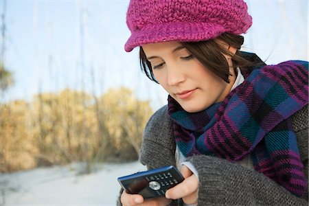 Teen girl text messaging at the beach Stock Photo - Premium Royalty-Free, Code: 632-03652033