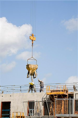 Construction workers guiding bucket suspended by crane to deposit concrete on building under construction Stock Photo - Premium Royalty-Free, Code: 632-03652208