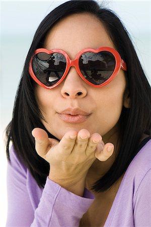 Woman wearing heart shaped sunglasses, blowing a kiss at camera Stock Photo - Premium Royalty-Free, Code: 632-03652296