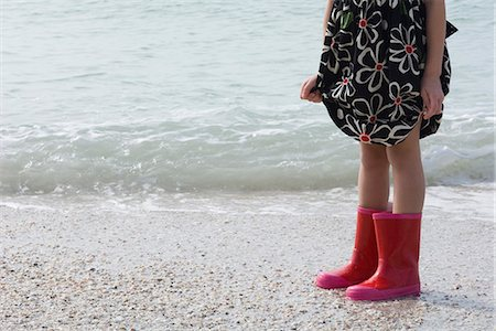 Girl standing on beach, wearing rubber boots Stock Photo - Premium Royalty-Free, Code: 632-03652329