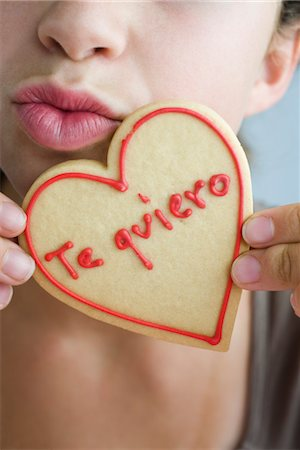 Woman puckering lips, holding heart-shaped cookie Stock Photo - Premium Royalty-Free, Code: 632-03754215