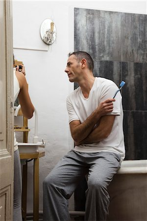 Husband waiting in bathroom while wife applies make-up Stock Photo - Premium Royalty-Free, Code: 632-03754314