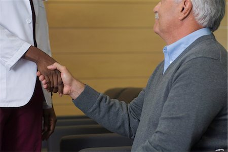 doctor in waiting room - Man shaking hands with healthcare worker in waiting room Stock Photo - Premium Royalty-Free, Code: 632-03754382