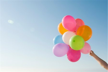 release - Bunch of helium balloons held aloft against clear blue sky Stock Photo - Premium Royalty-Free, Code: 632-03754514