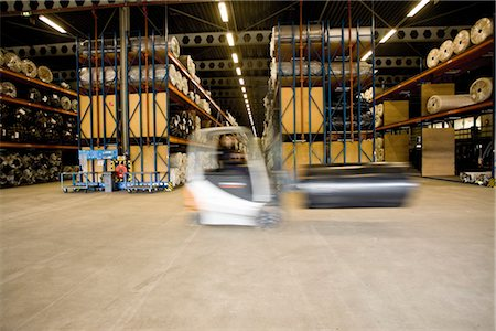 Forklift transporting roll in carpet tile factory warehouse Stock Photo - Premium Royalty-Free, Code: 632-03754584