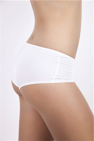 Young woman in underwear, side view of mid section Stock Photo - Premium Royalty-Free, Code: 632-03779368