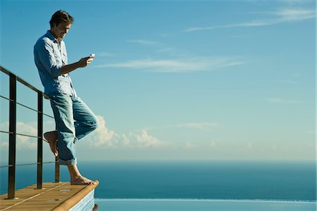 Man standing beside infinity pool, text messaging with cell phone Stock Photo - Premium Royalty-Free, Code: 632-03779586