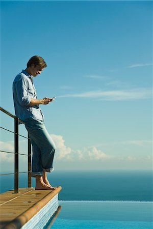 Man standing beside infinity pool, text messaging with cell phone Stock Photo - Premium Royalty-Free, Code: 632-03779596