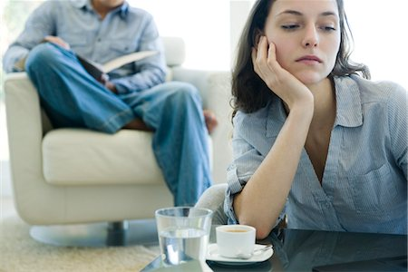 daily - Woman leaning on elbow looking sad, man reading on sofa in background Stock Photo - Premium Royalty-Free, Code: 632-03779750