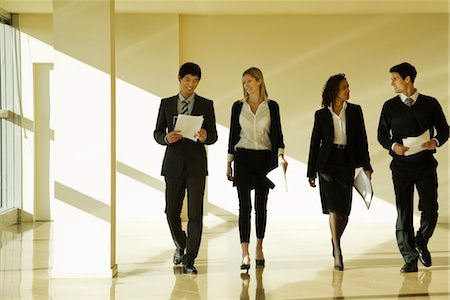dynamic - Group of business associates talking as they walk together in lobby Stock Photo - Premium Royalty-Free, Code: 632-03779784