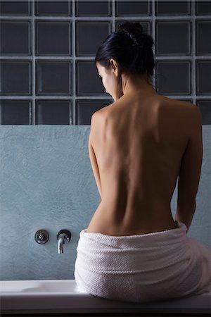Woman sitting on edge of bathtub, rear view Stock Photo - Premium Royalty-Free, Code: 632-03847703