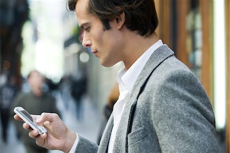 Man text messaging outdoors Stock Photo - Premium Royalty-Free, Code: 632-03847952