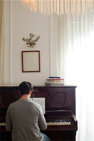Man playing piano, rear view Stock Photo - Premium Royalty-Free, Code: 632-03847995