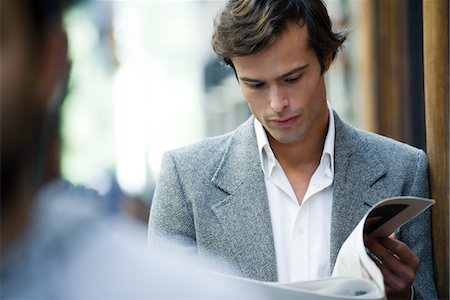 Man leaning against wall reading newspaper Stock Photo - Premium Royalty-Free, Code: 632-03848012