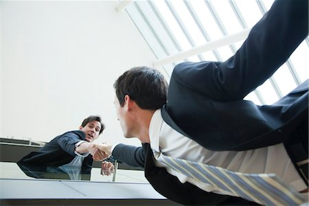 people falling - Businessman leaning over balcony, holding on to colleague's hand Stock Photo - Premium Royalty-Free, Code: 632-03848096