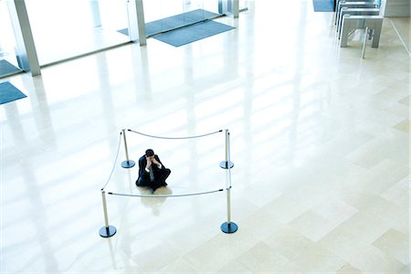 Businessman sitting on floor inside roped off area in lobby Foto de stock - Sin royalties Premium, Código: 632-03848105