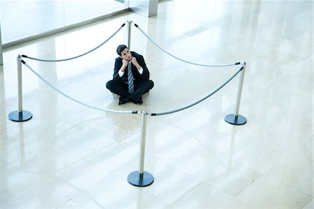 Businessman sitting on floor inside roped off area in lobby Foto de stock - Sin royalties Premium, Código: 632-03848110