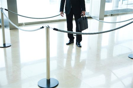 Businessman standing inside roped off area in lobby Foto de stock - Sin royalties Premium, Código: 632-03848129