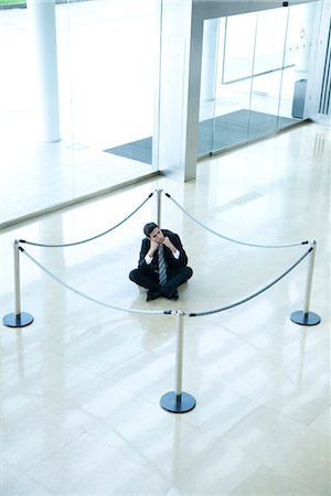 Businessman sitting on floor inside roped off area in lobby Foto de stock - Sin royalties Premium, Código: 632-03848157
