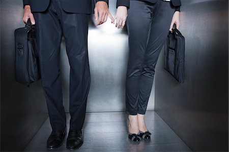 flirting - Colleagues holding hands in elevator, low section Stock Photo - Premium Royalty-Free, Code: 632-03848158