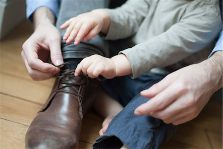 family shoes - Chhild helping father tie shoelace Stock Photo - Premium Royalty-Free, Code: 632-03848351