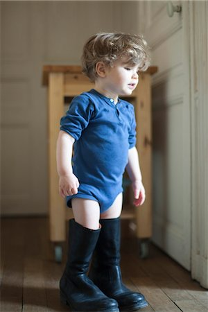 Toddler boy wearing father's boots Stock Photo - Premium Royalty-Free, Code: 632-03848383