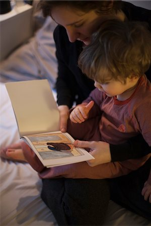 story - Mother holding toddler son on lap, reading bedtime story Stock Photo - Premium Royalty-Free, Code: 632-03897920