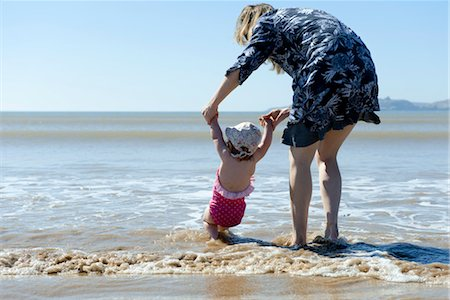 Mother and baby daughter walking in surf at the beach, rear view Stock Photo - Premium Royalty-Free, Code: 632-03898006