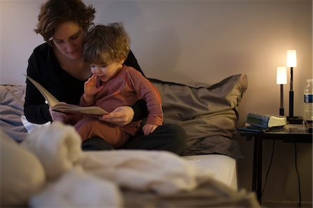 story - Mother holding toddler son on lap, reading bedtime story in bed Stock Photo - Premium Royalty-Free, Code: 632-03898120