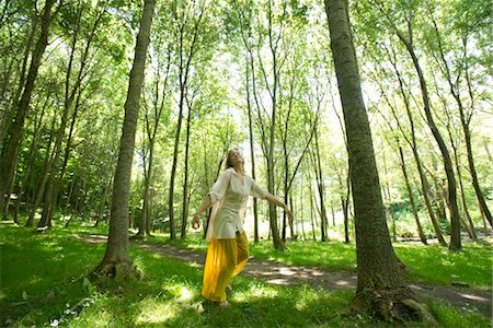 Young woman standing on one leg in woods Stock Photo - Premium Royalty-Free, Code: 633-05401428