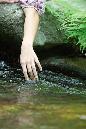 Young woman's hand touching water in stream Stock Photo - Premium Royalty-Free, Code: 633-05401441