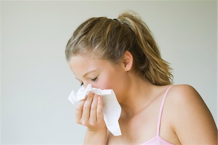 people coughing or sneezing - Young woman sneezing into tissue Stock Photo - Premium Royalty-Free, Code: 633-05401617