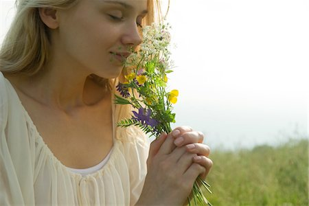 smelling - Young woman smelling bouquet of wildflowers, cropped Stock Photo - Premium Royalty-Free, Code: 633-05401795