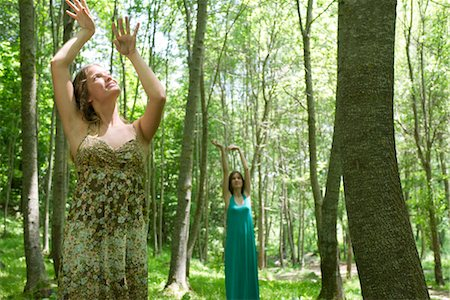 Young women in forest, arms raised toward sunlight Stock Photo - Premium Royalty-Free, Code: 633-05401796