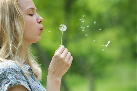 Young woman blowing dandelion flower Stock Photo - Premium Royalty-Free, Code: 633-05401915