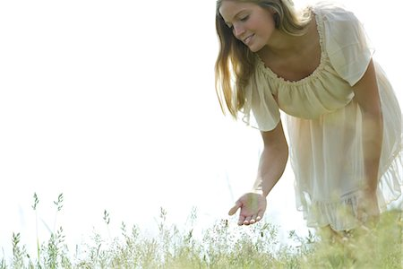 Young woman bending over to touch tall grass Stock Photo - Premium Royalty-Free, Code: 633-05401911